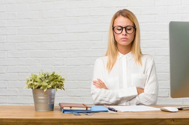 Ritratto di giovane studente seduto sulla sua scrivania facendo compiti molto arrabbiato e sconvolto, molto teso, urlando furioso, negativo e pazzo