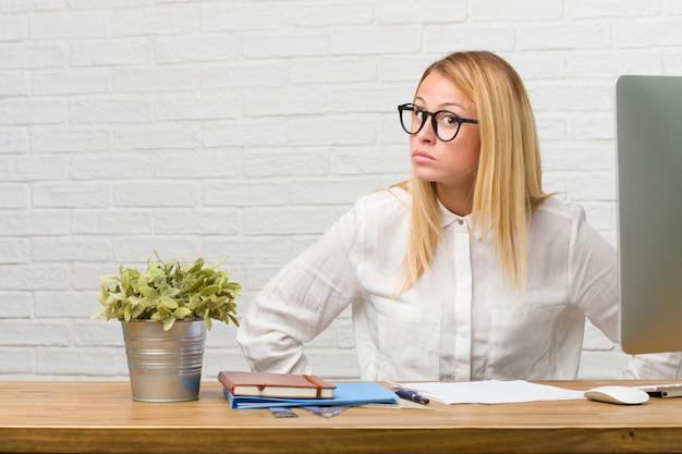 Ritratto di giovane studente seduto sulla sua scrivania facendo compiti molto arrabbiato e sconvolto