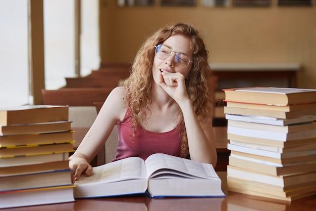 Ritratto di giovane studente sognante riflessivo seduto nella sala di lettura, mettendo la mano vicino al viso, toccando enorme libro aperto, guardando fuori dalla finestra, preparando per l'esame.