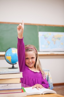 Ritratto di giovane studentessa alzando la mano