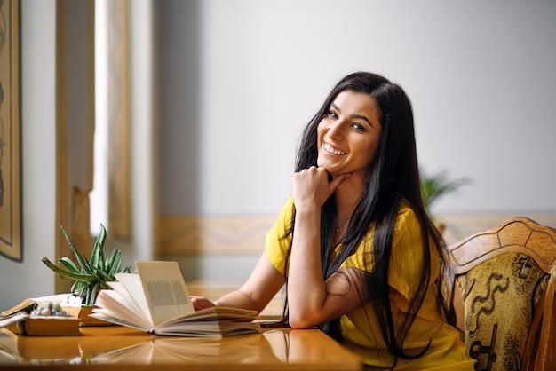 Ritratto di giovane studentessa entusiasta sorridente che studia con un libro alla biblioteca
