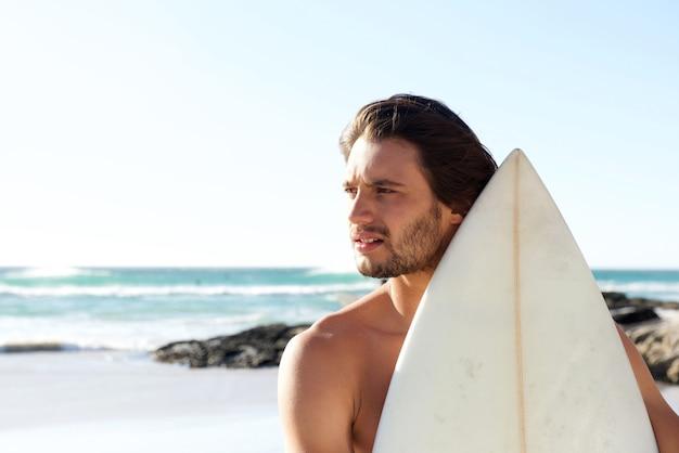 Ritratto di giovane surfista in spiaggia