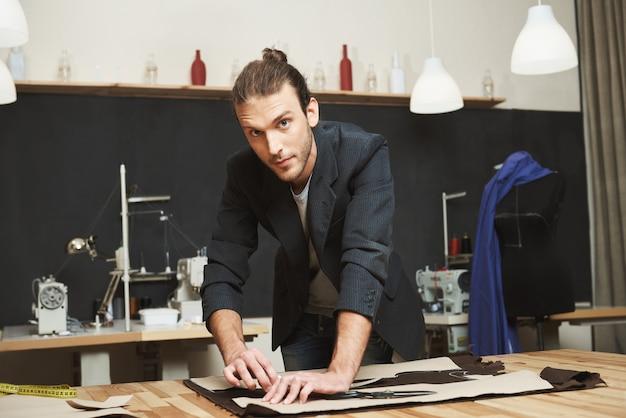 Ritratto di giovane talentuoso designer maschio bello con acconciatura alla moda e abbigliamento casual guardando a porte chiuse con espressione del viso concentrato mentre ritaglia parti del vestito della collezione primavera