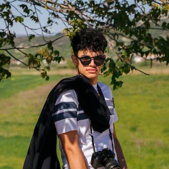 Ritratto di giovane uomo affascinante che indossa occhiali da sole e fotocamera digitale che guarda l'obbiettivo