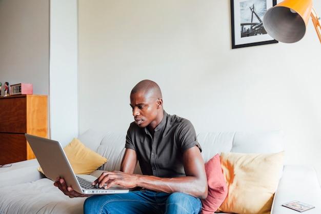 Ritratto di giovane uomo africano che per mezzo del computer portatile a casa