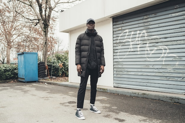 Ritratto di giovane uomo africano che sta nella via e che guarda macchina fotografica