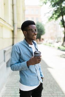 Ritratto di giovane uomo africano felice che cammina sulla strada con la tazza di caffè.