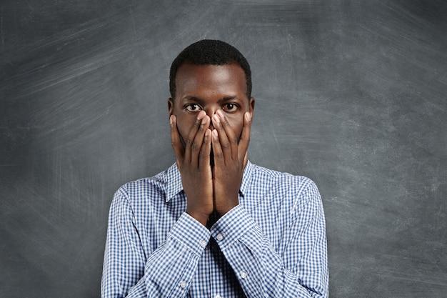 Ritratto di giovane uomo afro-americano in camicia a scacchi che copre la bocca con entrambe le mani e guardando con espressione scioccata e colpevole come se avesse fatto qualcosa di sbagliato, in piedi alla lavagna vuota