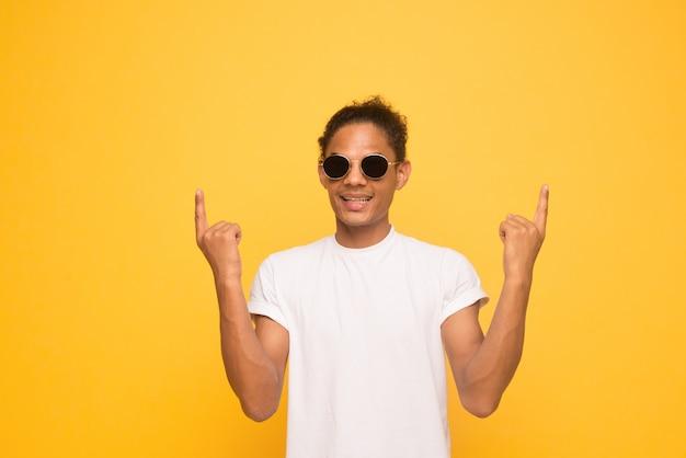 Ritratto di giovane uomo afroamericano bello felice con casual sorridente in bicchieri, rivolto verso l'alto con il dito,