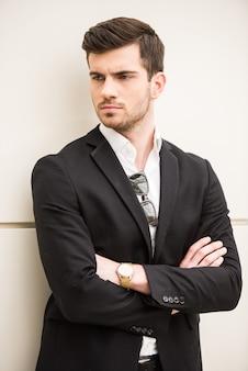 Ritratto di giovane uomo alla moda è in posa davanti a un muro.
