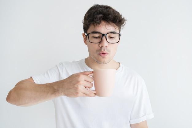 Ritratto di giovane uomo asiatico che soffia al caffè caldo nella tazza