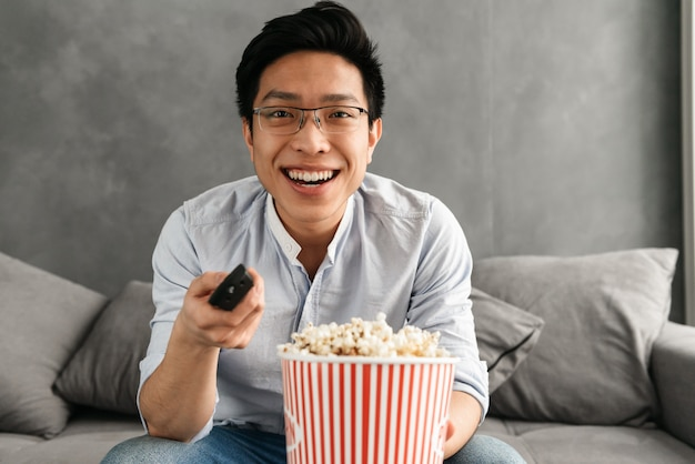 Ritratto di giovane uomo asiatico felice che tiene popcorn