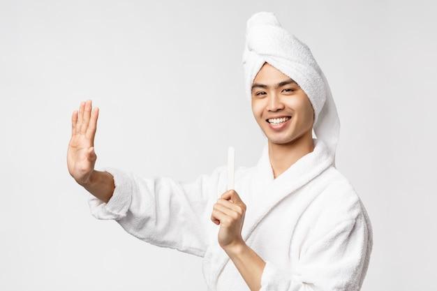 Ritratto di giovane uomo asiatico in accappatoio che mostra gesto. dopo la doccia