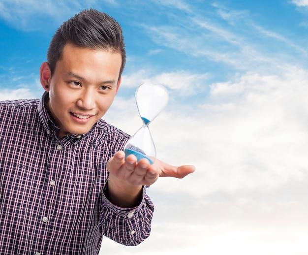 Ritratto di giovane uomo asiatico in possesso di un temporizzatore della sabbia