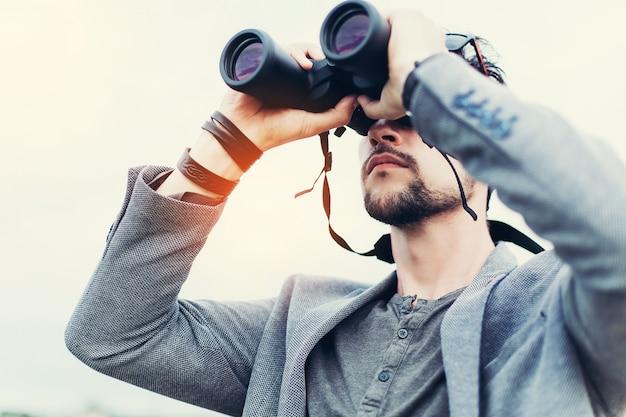 Ritratto di giovane uomo avventura che viaggia con il binocolo
