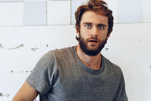 Ritratto di giovane uomo barbuto espressivo spaventato e nervoso