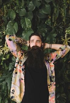 Ritratto di giovane uomo barbuto lungo in piedi di fronte a foglie verdi