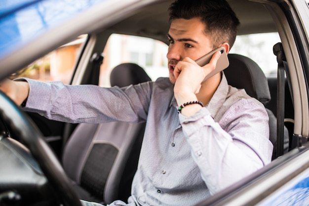 Ritratto di giovane uomo bello che conduce automobile e che parla sul telefono cellulare.