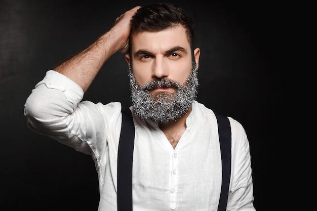 Ritratto di giovane uomo bello con la barba nella neve sopra il nero.