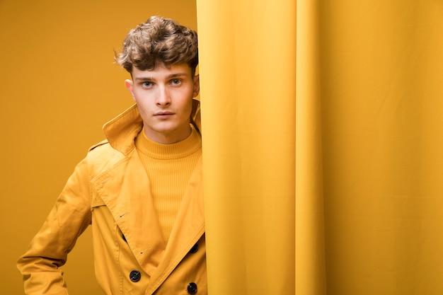 Ritratto di giovane uomo bello in una scena gialla