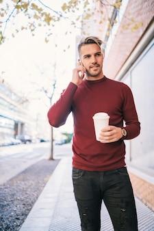 Ritratto di giovane uomo bello parlare al telefono mentre si tiene una tazza di caffè all'aperto in strada. concetto di comunicazione.