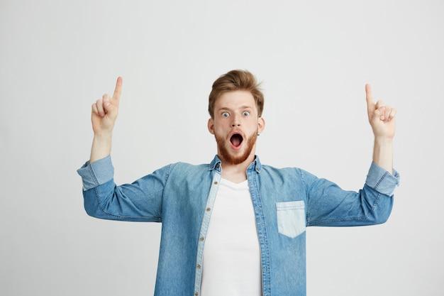 Ritratto di giovane uomo bello sorpreso con la bocca aperta che indica dito su.