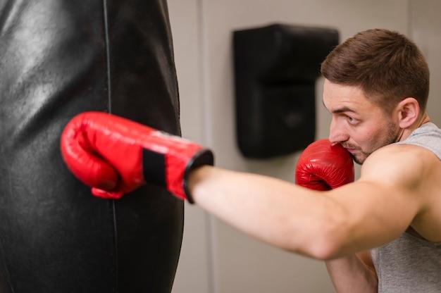 Ritratto di giovane uomo boxe in palestra