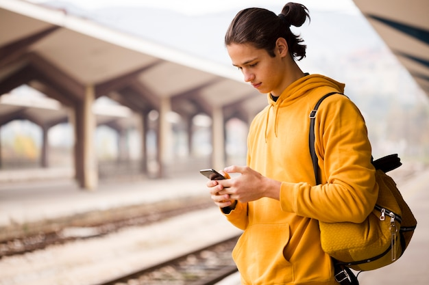 Ritratto di giovane uomo che controlla il suo telefono