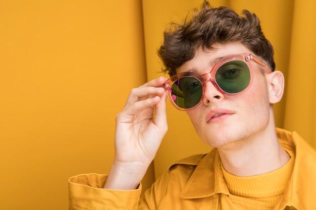 Ritratto di giovane uomo con gli occhiali da sole in una scena gialla