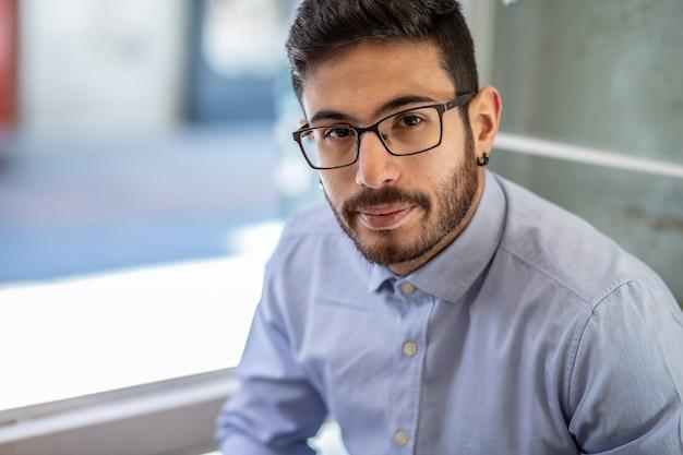 Ritratto di giovane uomo con gli occhiali e la camicia blu