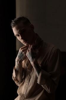 Ritratto di giovane uomo con gocce d'acqua sul viso sul muro scuro