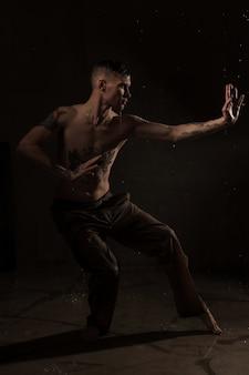 Ritratto di giovane uomo con gocce d'acqua sulla parete nera