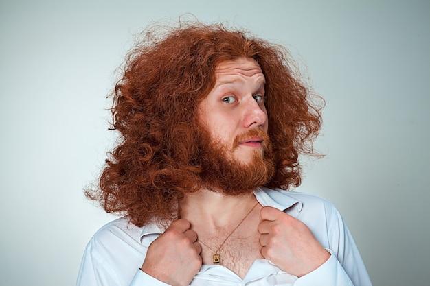 Ritratto di giovane uomo con lunghi capelli rossi e con espressione facciale scioccata su sfondo grigio