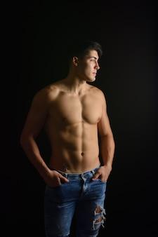 Ritratto di giovane uomo con torso nudo con jeans su sfondo nero