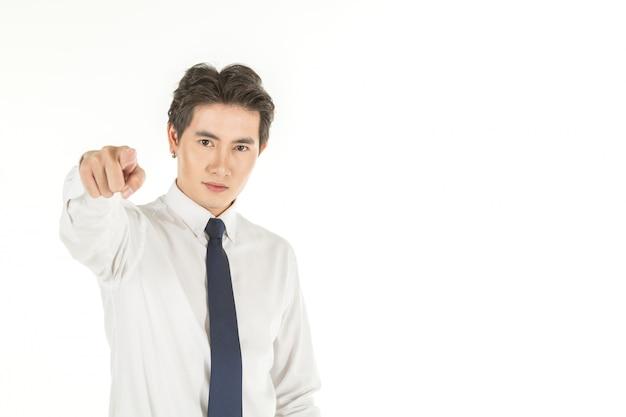 Ritratto di giovane uomo d'affari asiatico astuto con la camicia bianca e il legame blu che indica dito sullo spazio bianco isolato della copia e del fondo.