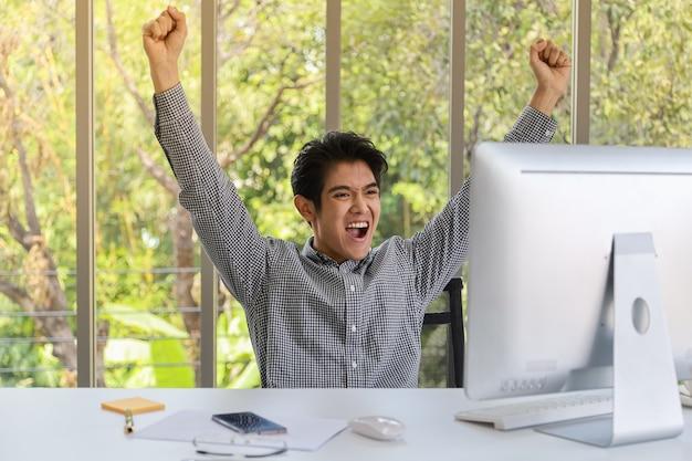 Ritratto di giovane uomo d'affari asiatico astuto felice che guarda al desktop computer e serra due pugni ed emozione felici nella stanza di lavoro.