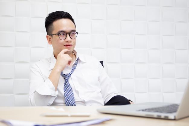 Ritratto di giovane uomo d'affari asiatico astuto nell'ufficio.