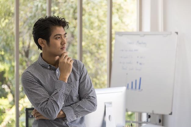 Ritratto di giovane uomo d'affari asiatico astuto nella stanza dell'ufficio con il computer e bordo di riunione con l'istogramma. immagine per affari e concetto di lavoro.