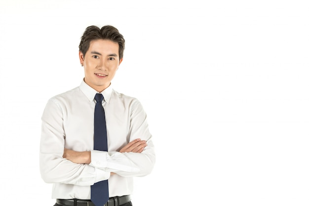 Ritratto di giovane uomo d'affari asiatico sorridente astuto con la camicia bianca e legame blu sullo spazio bianco isolato della copia e del fondo.