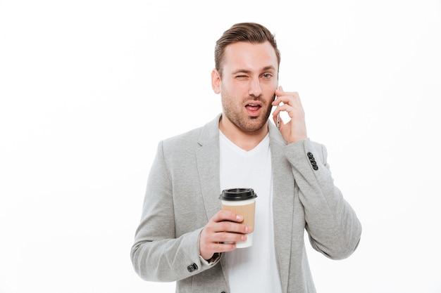 Ritratto di giovane uomo d'affari che beve caffè asportabile pur avendo piacevole conversazione mobile sul cellulare e sbattere le palpebre, sopra la parete bianca