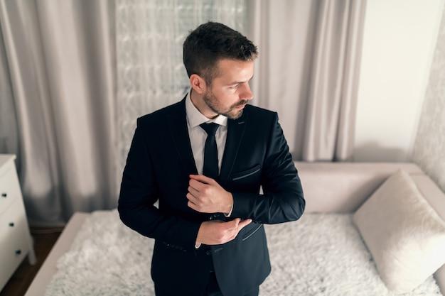 Ritratto di giovane uomo d'affari che lega i gemelli sulla giacca e distoglie lo sguardo.