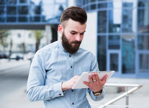 Ritratto di giovane uomo d'affari che sta fuori dell'edificio per uffici facendo uso della compressa digitale