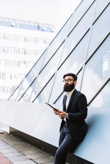 Ritratto di giovane uomo d'affari che tiene compressa digitale a all'aperto
