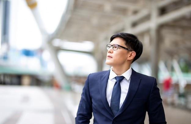 Ritratto di giovane uomo d'affari con braccio incrociato contro edificio sfocato