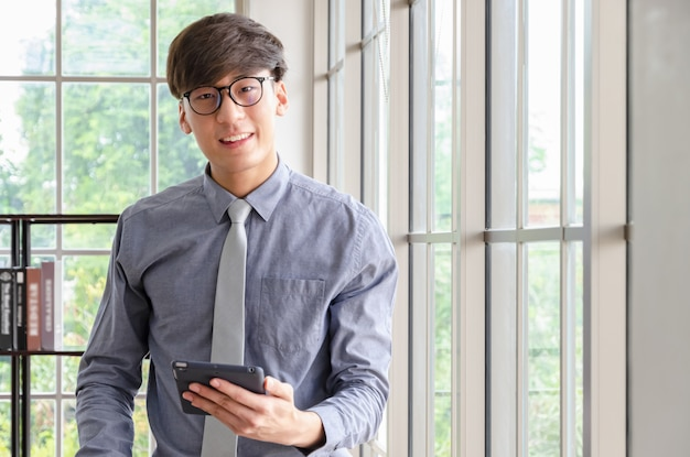 Ritratto di giovane uomo d'affari con il pc della compressa in ufficio con le luci del salice