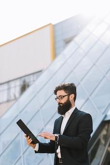 Ritratto di giovane uomo d'affari guardando la tavoletta digitale