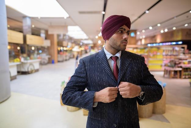 Ritratto di giovane uomo d'affari indiano bello sikh che indossa turbante mentre esplora la città di bangkok, thailandia