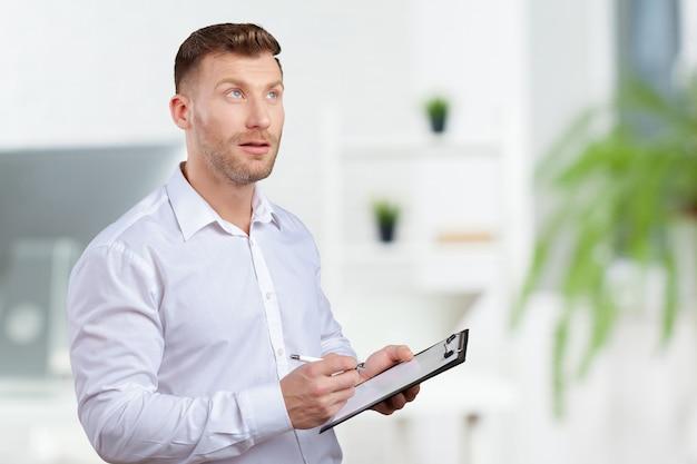 Ritratto di giovane uomo d'affari prendendo appunti