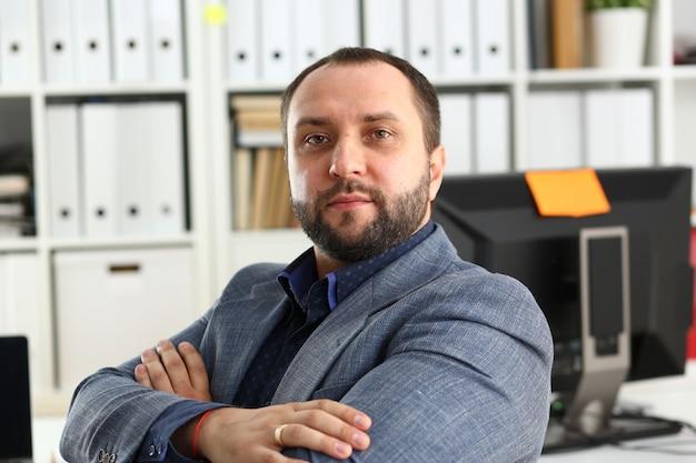 Ritratto di giovane uomo d'affari promettente bello in ufficio