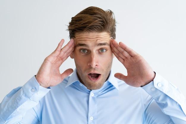 Ritratto di giovane uomo d'affari sollecitato che massaggia la testa facente male